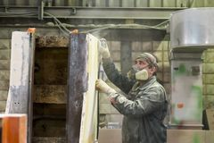 The worker polishes the primer layer. Work on the preparation of the machine bed for subsequent painting. Stock Photo