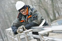 Worker polishing metal fence barrier Stock Photos