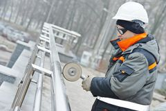 Worker polishing metal fence barrier Royalty Free Stock Photography