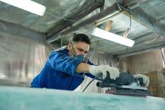 Worker Polishing Motorboat in Workshop. Portrait of mature modern man wearing respirator repairing boats in workshop using electric polishing tool, copy space stock image