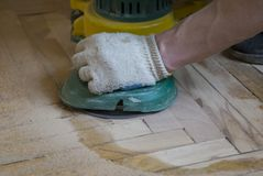 Worker polishing old wooden parquet floor. With grinding machine stock images