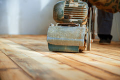 Worker polishing parquet floor with grinding machine Royalty Free Stock Images