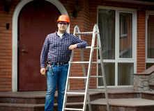 Worker posing with metal ladder against building house Stock Photo
