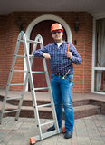 Worker posing with tools against house entrance Stock Images