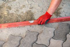 The worker positioning the bricks on the patio Royalty Free Stock Photos
