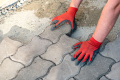 The worker positioning the bricks on the patio Royalty Free Stock Image