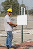 Worker Posting Blank Sign. Construction worker posting a blank sign on location Royalty Free Stock Images