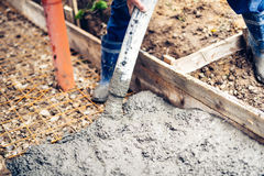 Worker pouring cement and concrete with pump tube on reinforcement steel bars Stock Photography