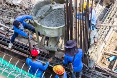 Worker pouring cement pouring into foundations formwork at building area in construction site royalty free stock photography