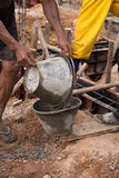 Worker pouring concrete from pail bucket. At construction site Stock Image