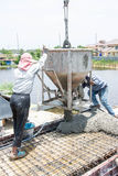 Worker pouring concrete works at construction site Stock Photography