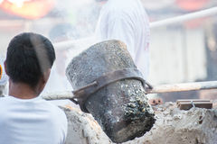 Worker pouring molten metal to casting Buddha statue Royalty Free Stock Images