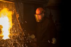 The worker pours the melted metal from the furnace into the ladle Royalty Free Stock Photos