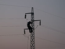 Worker on power line pylon. Silhouette of a worker on maintenance job on high voltage pole, featuring three phase wires shorted and grounded for security Royalty Free Stock Photography