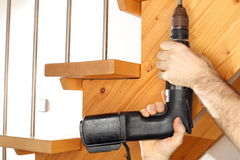 Worker with power screwdriver is fixing stairs Royalty Free Stock Photography