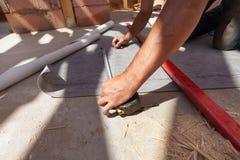 Worker prepare to cut the vapor barrier water resistant / vapor permeable / roof foil. Stock Photos