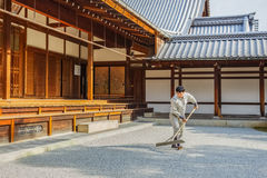 Worker prepares the rock garden at Kinkakuji Temple Royalty Free Stock Photography