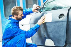 Worker preparing car body for paint. Auto mechanic worker applying washing car body preparing for painting at automobile repair and renew service station Royalty Free Stock Photo