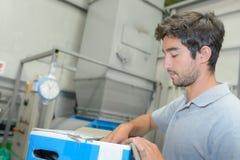 Worker preparing contents carton Stock Photos
