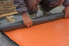 Worker preparing insulation material for basement wall 4 Stock Images