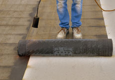 Worker preparing part of bitumen roofing felt roll. For melting by gas heater torch flame Royalty Free Stock Photos