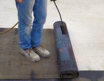 Worker preparing part of bitumen roofing felt roll Stock Images