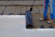 Worker preparing part of bitumen roofing felt roll Royalty Free Stock Images