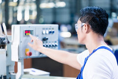 Worker pressing buttons on CNC machine in factory. Worker pressing buttons on CNC machine control board in Asian factory Royalty Free Stock Photography