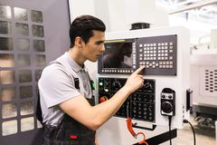 Worker pressing buttons on CNC machine royalty free stock image
