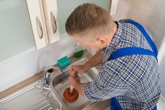 Worker Pressing Plunger In Sink Stock Photos