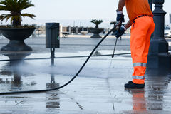 A worker with a pressure washer. Cleaning the street Royalty Free Stock Photo