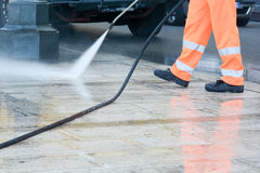 A worker with a pressure washer. Cleaning the street royalty free stock images