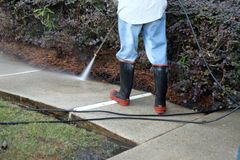 Worker pressure washing sidewalk stock photo