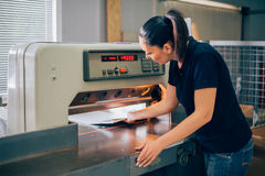 Worker in printing centar uses paper guillotine machine knife Royalty Free Stock Image