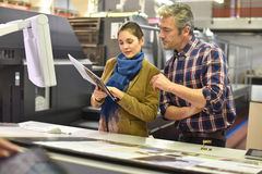 Worker in printing house showing prints to client Royalty Free Stock Photo