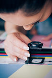 Worker in printing and press centar uses a magnifying glass stock photo