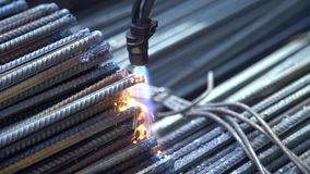A worker processes the edges of metal pins with a flame of a welding machine at a metal base stock footage