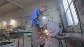 A worker processes a part on a grinding wheel. Sparks from the grinding wheel. Factory workflow