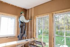 Construction worker thermally insulating eco wooden frame house. The worker produces finishing works of the ceiling with a white wooden board. Construction royalty free stock image