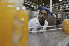 Worker on production line looking down conveyor belt stock photo