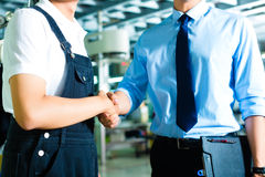 Worker and production manager in a factory. Worker or production manager and owner, ceo or controller shake hands in a factory Royalty Free Stock Photography