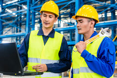 Worker in production plant with laptop Royalty Free Stock Photo