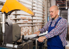 Worker at professional lathe. Portrait of middle age worker at professional lathe in plant Royalty Free Stock Images