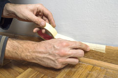 Worker protecting batten moulding with masking tape before paint Stock Photography