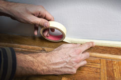 Worker protecting batten moulding with masking tape before paint Stock Photo