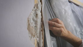 Worker protecting batten moulding with masking tape before painting at home improvement work. stock video footage