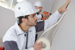 Worker protecting batten moulding with masking tape before painting. Young royalty free stock image