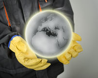Worker with protective gloves holding earth globe Royalty Free Stock Image