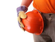 Worker in protective gloves holds an orange hard hat in his hand. Safety helmet. Royalty Free Stock Photography