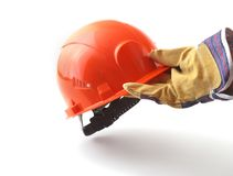 Worker in protective gloves holds an orange hard hat in his hand. Safety helmet. Stock Image